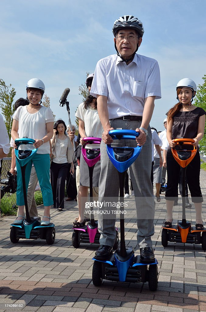 Toyota Motor partner robot director Akifumi Tamaoki (2nd R) and Tsukuba City Hall employees ride on Toyota's transport assistance robot, called the 'Winglet', during a public demonstration on a public sidewalk in Tsukuba City, suburban Tokyo on July 23, 2013. Toyota and Tsukuba City started to field test the next generation of 'personal mobility robot' on the public thoroughfare, with trial runs scheduled until 2016. AFP PHOTO / Yoshikazu TSUNO