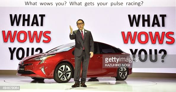 Toyota Motor president Akio Toyoda delivers a speech in front of the company's next generation hybrid vehicle Prius during a press briefing at the...