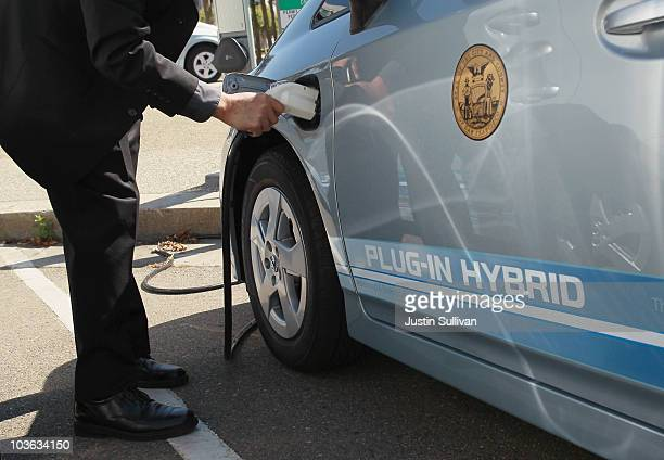 Toyota representative plugs a power cable from a vehicle charging station into the side of a Toyota Prius plugin hybrid August 25 2010 in San...