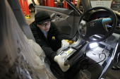 Toyota service technician Tungyio Saelee performs a recall repair on a brand new Toyota Camry at City Toyota February 5 2010 in Daly City California...