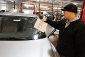 Toyota service technician Tungyio Saelee removes a 'not for sale' sign from a brand new Toyota Camry after he performed a recall repair on an...