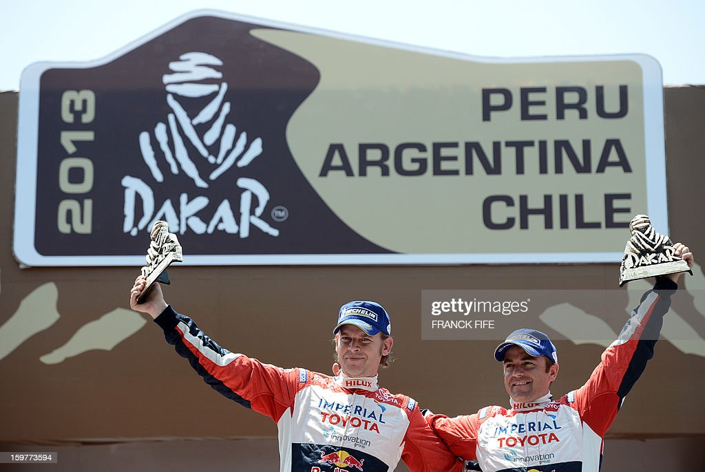 Toyota's driver Giniel De Villiers (R) of South Africa and co-driver Dirk Von Zitzewitz pose on the podium of the Dakar 2013 in Santiago, Chile on January 20, 2013. Mini's driver Stephane Perterhansel of France won the Dakar 2013 ahead of Toyota's driver Giniel De Villiers and Mini's driver Leonid Novitskiy of Russia.