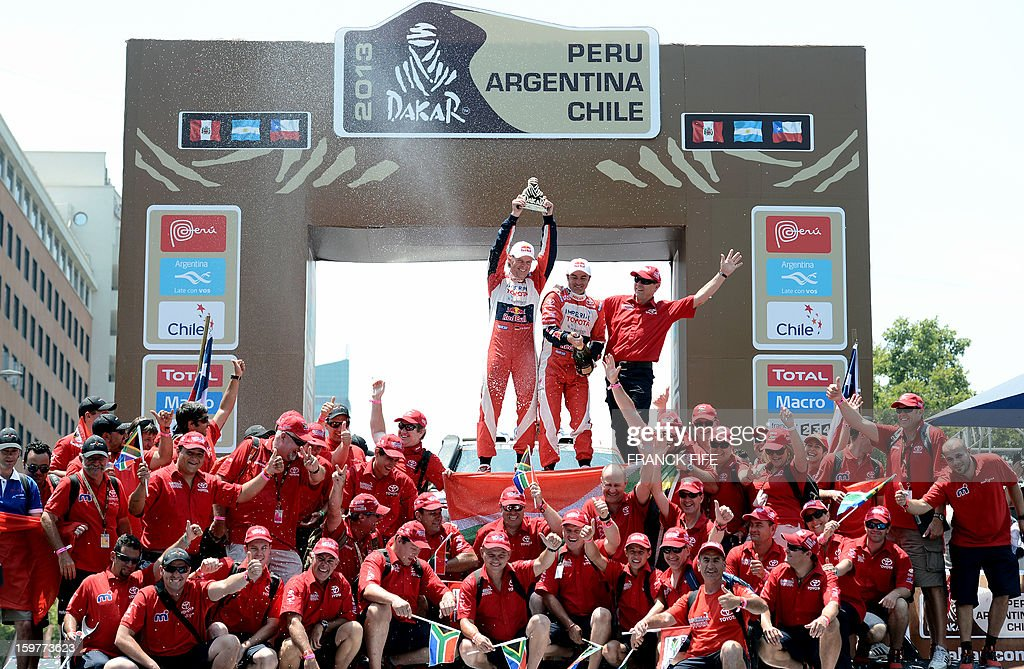 Toyota's driver Giniel De Villiers (C) of South Africa and co-driver Dirk Von Zitzewitz pose on the podium of the Dakar 2013 in Santiago, Chile on January 20, 2013. Mini's driver Stephane Perterhansel of France won the Dakar 2013 ahead of Toyota's driver Giniel De Villiers and Mini's driver Leonid Novitskiy of Russia.