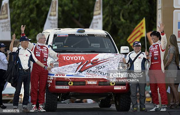 Toyotas driver Jun Mitsuhashi of Japan and codriver Alain Guehennec of France pose at the podium during the symbolic start of the 2014 Dakar Rally in...