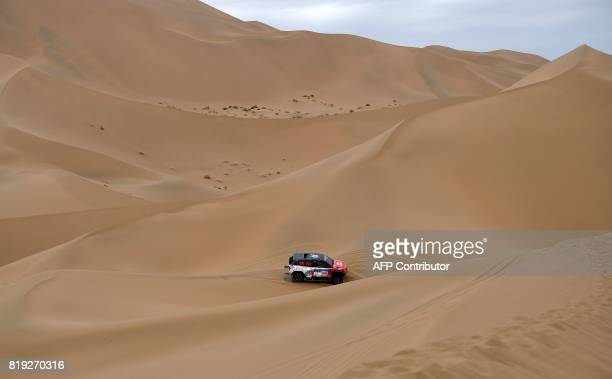 Toyota's French driver Christian Lavieille and codriver Jean Pierre Garcin ride over sand dunes as they compete during the Stage 12 of the Silk Way...