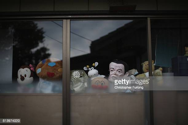 Toys and novelty masks look out from the window of a home inside the radiation contamination exclusion zone close to the devastated Fukushima Daiichi...