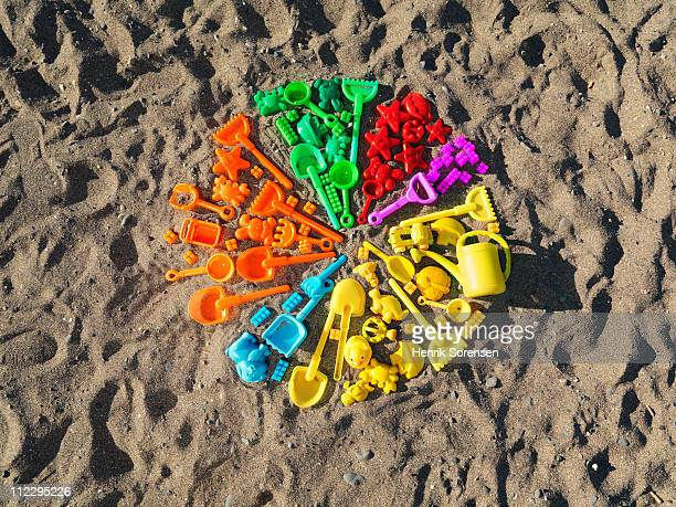Toys on beach sand forming a pie chart
