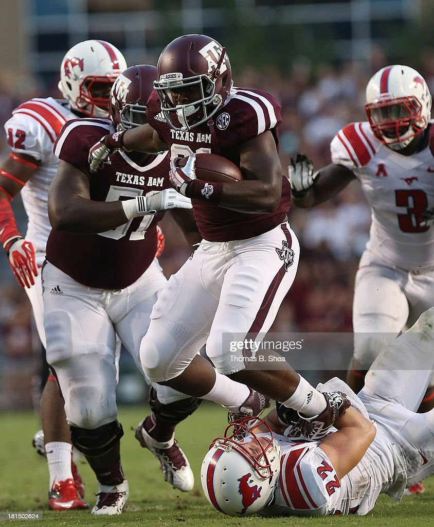 Tra Carson #21 of the Texas A&M Aggies runs over Hayden Greenbauer #22 of the Southern Methodist Mustangs in the second half on September 21, 2013 at Kyle Field in College Station, Texas.