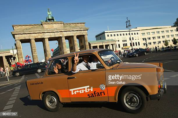 Trabant car operated by Trabi Safari drives past the Brandenburg Gate on September 8 2009 in Berlin Germany Trabi Safari takes tourists on tours...