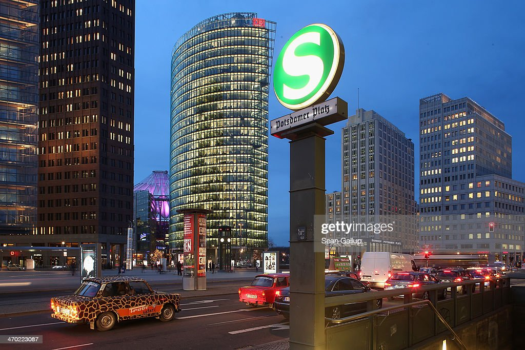 Trabant cars ferrying tourists on an urban safari stand at Potsdamer Platz at dusk while the headquarters of Deutsche Bahn loom behind on February 18, 2014 in Berlin, Germany. Potsdamer Platz is among the city's major landmarks.