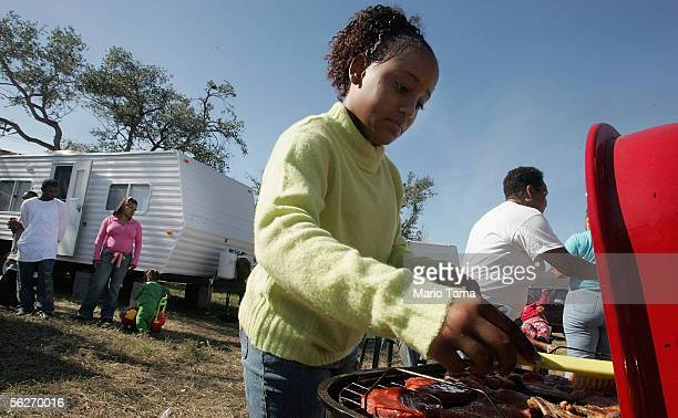 Trachelle Blanchard bastes meat over a grill for a makeshift Thanksgiving meal outside the trailers her family is living in on November 24 2005 in...