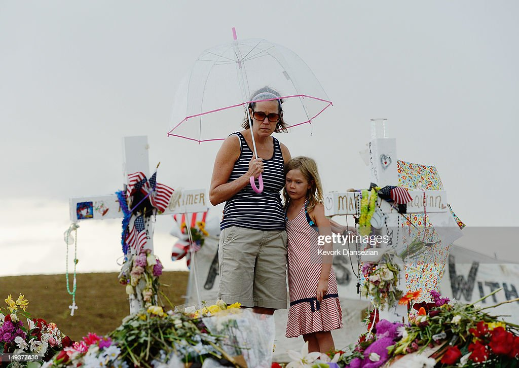 Traci Gillespie and her daughter Avery Gillespie, 7, visit a memorial setup across the street from the Century 16 movie theatre on July 27, 2012 in Aurora, Colorado. Twenty-four-year-old James Holmes is suspected of killing 12 and injuring 58 others July 20 during a shooting rampage at a screening of 'The Dark Knight Rises' in Aurora, Colorado.