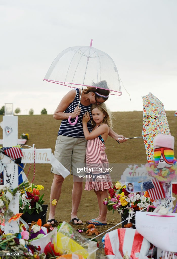 Traci Gillespie kisses her daughter Avery Gillespie, 7, during their visit to a memorial setup across the street from the Century 16 movie theatre on July 27, 2012 in Aurora, Colorado. Twenty-four-year-old James Holmes is suspected of killing 12 and injuring 58 others July 20 during a shooting rampage at a screening of 'The Dark Knight Rises' in Aurora, Colorado.