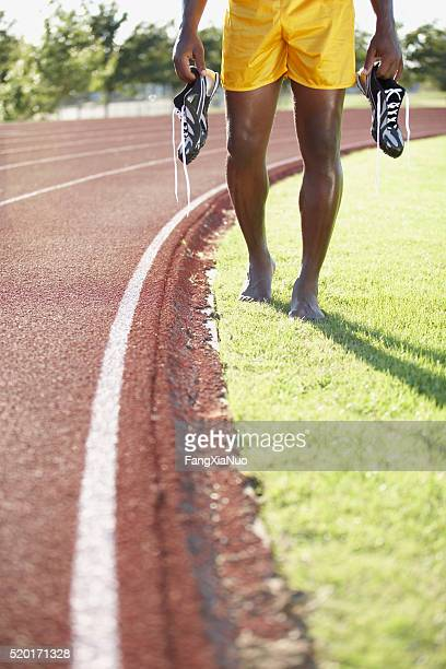 Track and field athlete holding his shoes