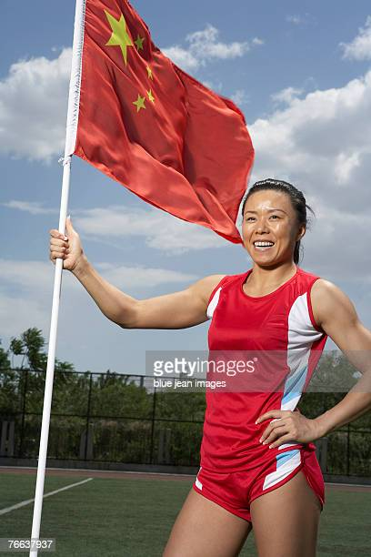 A track and field athlete is standing with the Chinese flag.