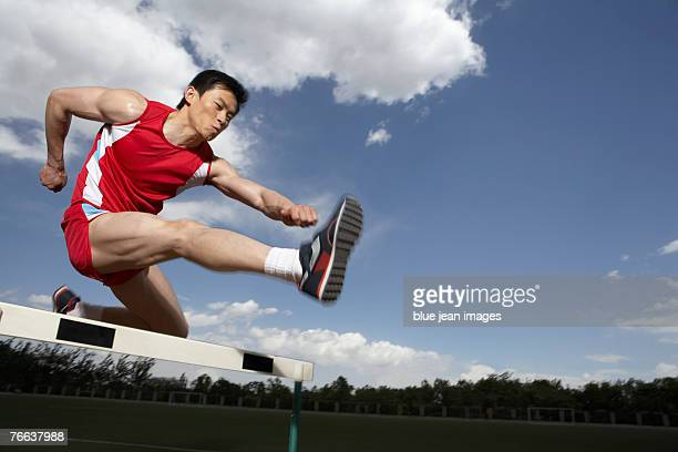 A track and field athlete jumps a hurdle.