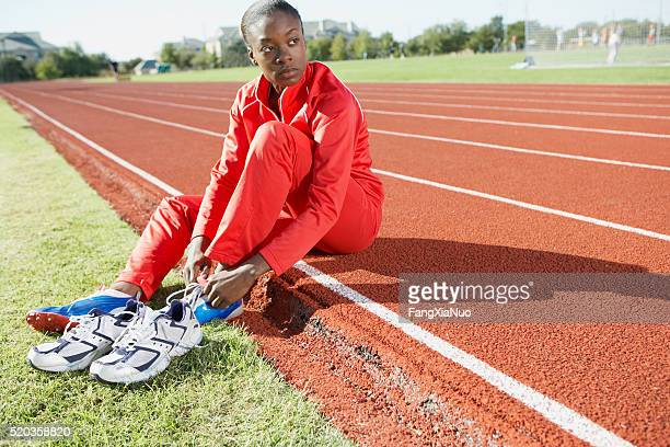 Track and field athlete putting on shoes