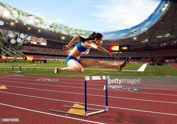 Track and field athletes in hurdle race