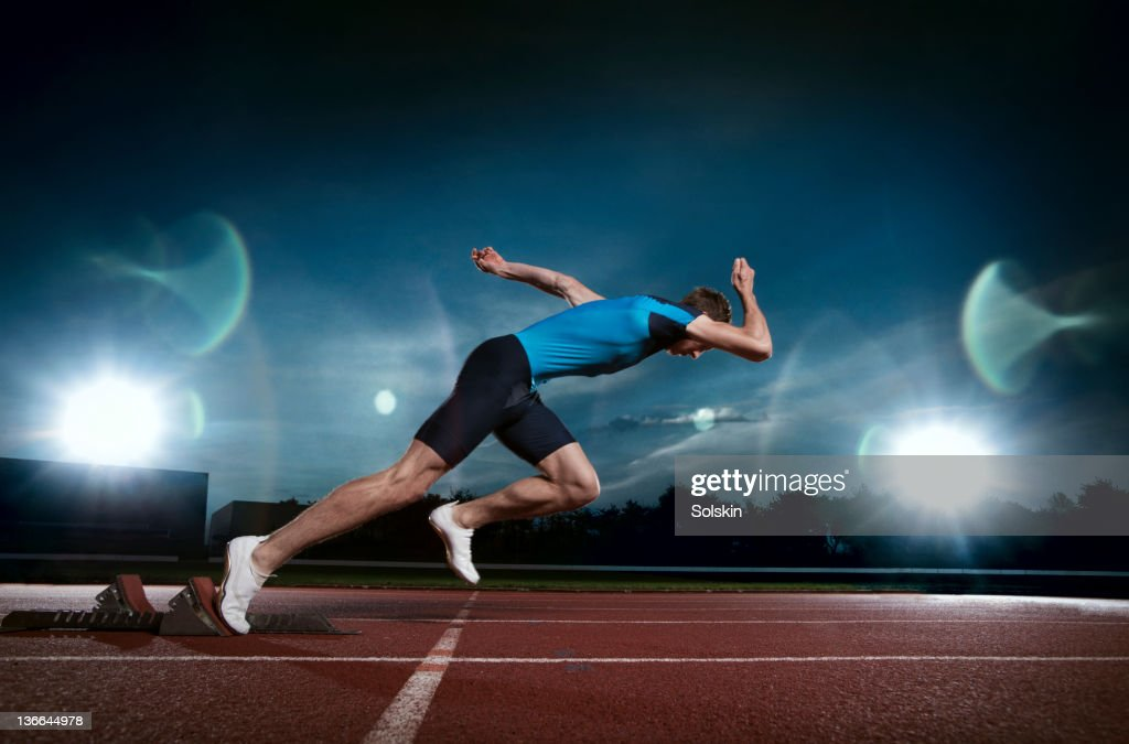Track and field sprinter coming out of blocks : Stockfoto