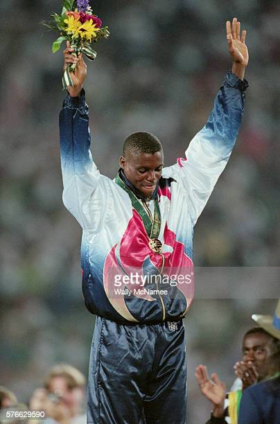 Track and field star Carl Lewis receives the long jump gold medal at Atlanta's Olympic Stadium during the 1996 Olympic Games