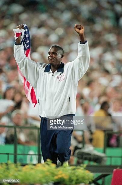 Track and field star Carl Lewis waves the US flag at Atlanta's Olympic Stadium during the 1996 Olympic Games Lewis won the gold medal in the long...