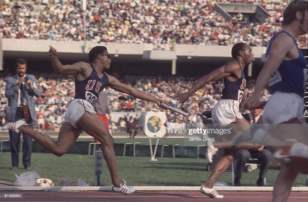 1968 Summer Olympics, USA Ronnie Ray Smith (306) in action, handing baton to teammate Jim Hines (279) during 4X100M relay race, Mexico City, MEX --