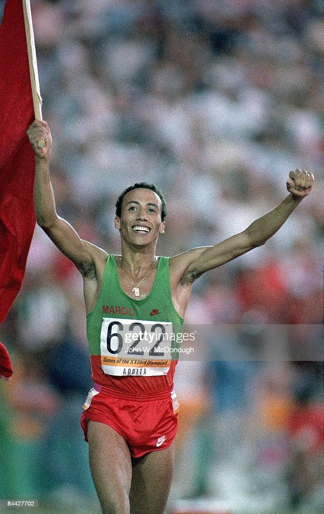 1984 Summer Olympics Morocco Said Aouita victorious with flag on track after winning Men's 5000M gold medal at Memorial Coliseum Los Angeles CA...