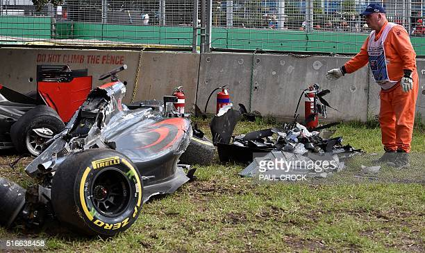 A track marshall drops pieces of detached wreckage of the McLaren Honda car of Spanish driver Fernando Alonso into a pile after he crashed...