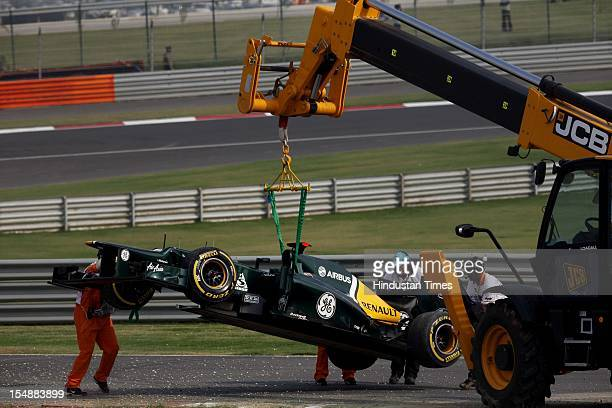 Track marshals hoist the car of CaterhamRenault driver Heikki Kovalainen of Finland after he skid off the track during the qualifying session at The...
