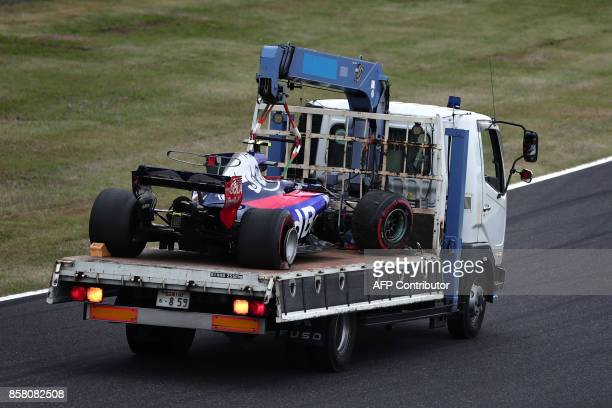 Track marshals take the damaged car of Toro Rosso's Spanish driver Carlos Sainz Jr back to the pits after he crashed during the first practice round...
