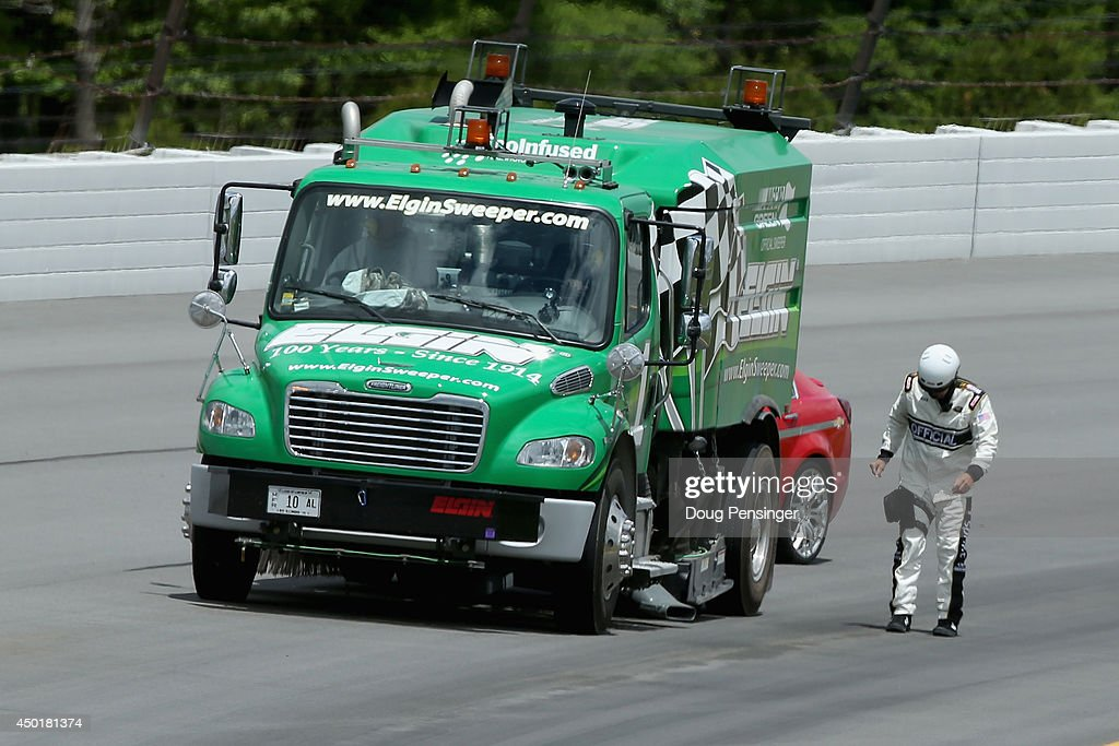 A track official inspects the track surface for water as clean-up vehicles word under caution during practice for the NASCAR Sprint Cup Series Pocono 400 at Pocono Raceway on June 6, 2014 in Long Pond, Pennsylvania.