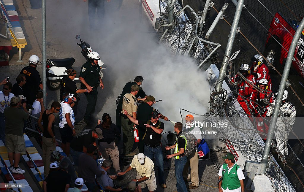 Track officials put out flames after an incident at the finish of the NASCAR Nationwide Series DRIVE4COPD 300 at Daytona International Speedway on February 23, 2013 in Daytona Beach, Florida.
