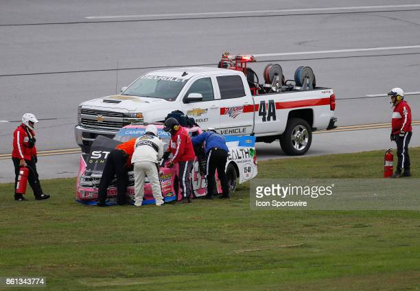 Track officials tend to the wrecked truck of Kaz Grala Chevrolet Silverado during the Fred's 250 NASCAR Camping World truck race on October 14 at the...