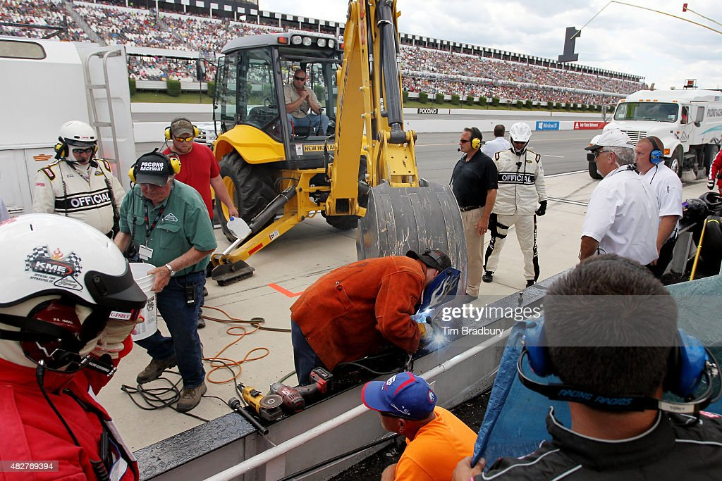 Track officials work to repair a section of the pit wall damaged in an ontrack incident involving Kasey Kahne driver of the Aquafina Chevrolet during...