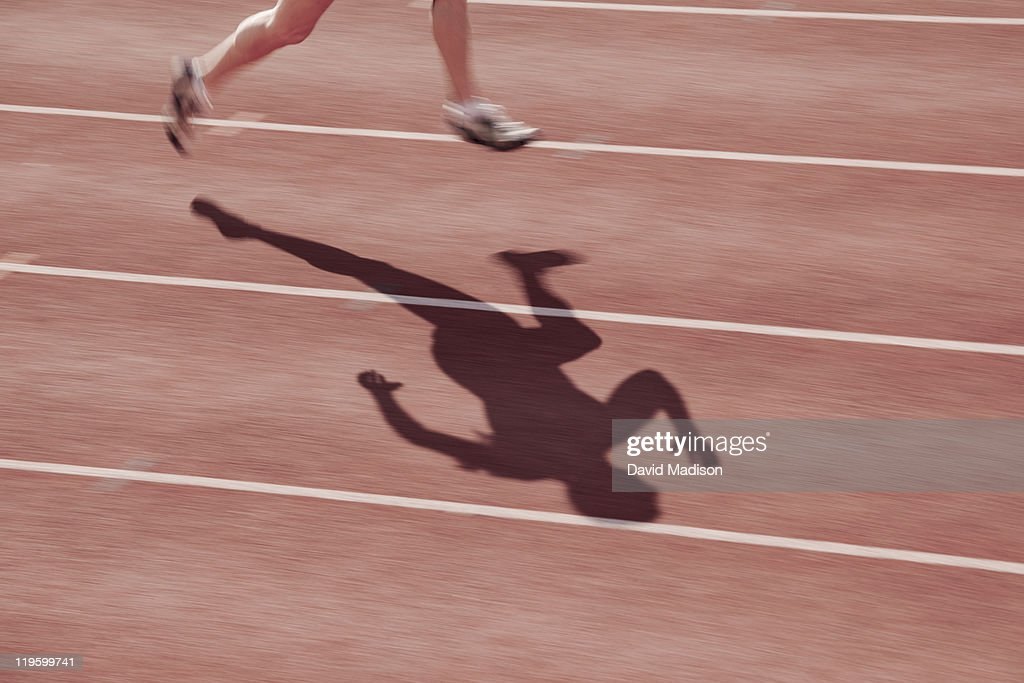Track runner and shadow. : Stock Photo