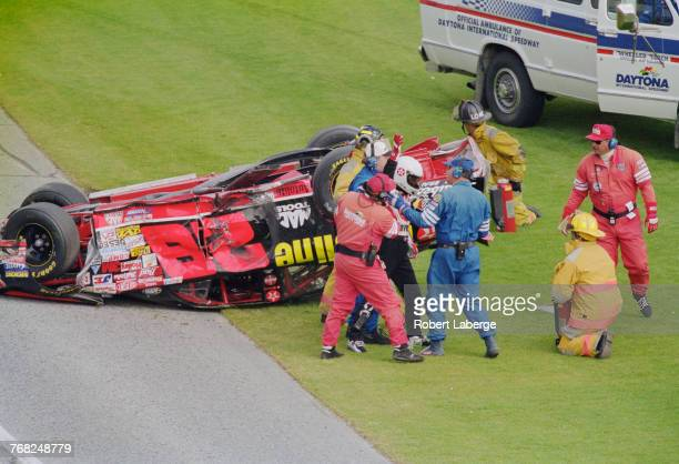 Track safety marshals come to the aid of Ricky Rudd after the Yates Racing Texaco Havoline Ford Taurus crashes and overturns following a collision...