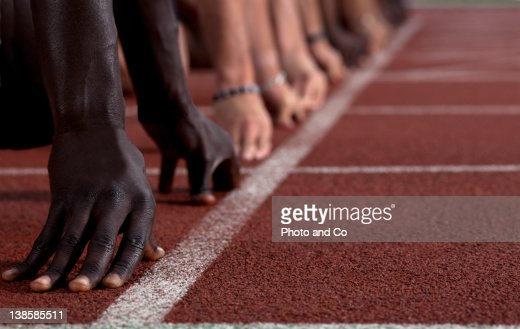 Track sprinters lined up at starting line : Stock Photo