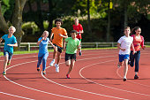 Panning shot of a group of teenagers running a track race.