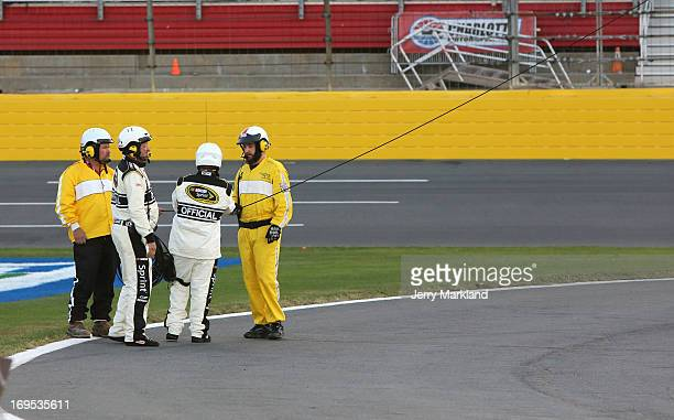 Track workers and NASCAR Officials clean up cable from an aerial Fox Sports camera on the front stretch during a red flag in the NASCAR Sprint Cup...