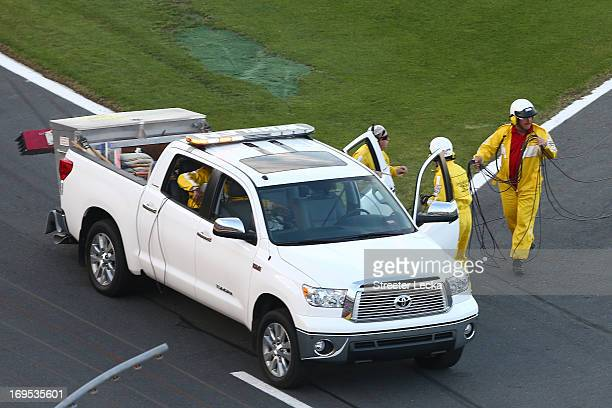 Track workers clean up cable from an aerial Fox Sports camera on the front stretch during a red flag in the NASCAR Sprint Cup Series CocaCola 600 at...