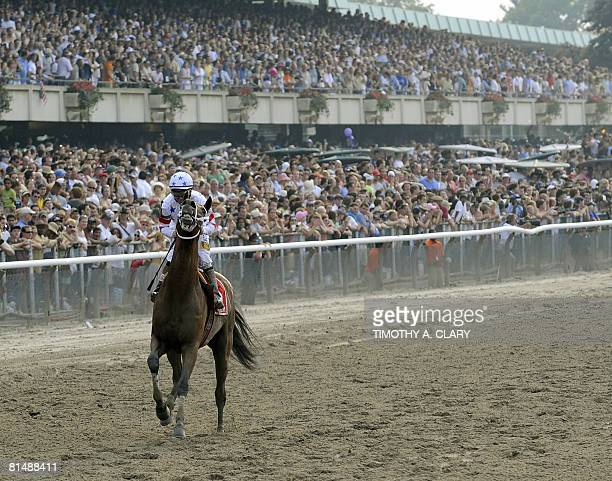 Track workers rush to the aid of Big Brown with jockey Kent Desormeaux aboard as he makes his way to the finish line after failing to finish the...