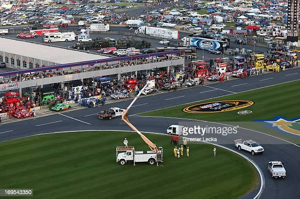Track workers take down an aerial Fox Sports camera in the infield from a cherry picker during a red flag in the NASCAR Sprint Cup Series CocaCola...