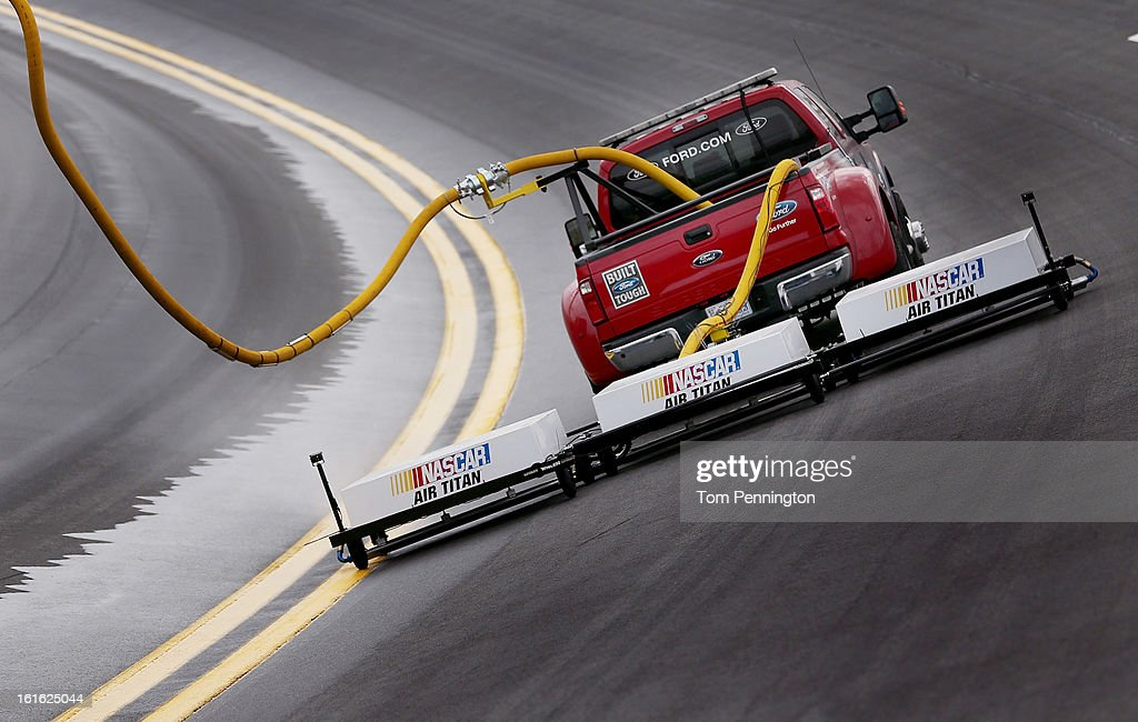 Track workers test the new NASCAR Air Titan track dryer at Daytona International Speedway on February 13, 2013 in Daytona Beach, Florida. The new dryer system uses compressed air to force standing water from the racing surface faster than the existing jet dryer system.