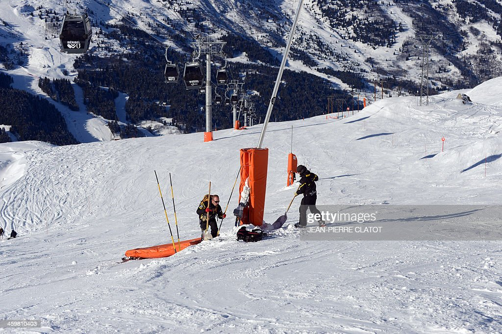 Trackers secure a pylon on December 31, 2013 on a slope of the French Alps ski resort of Meribel not far from the site where German retired Formula One legend Michael Schumacher had an accident on December 29. Schumacher's condition has shown a slight improvement after a second operation following his weekend ski accident but he is not out of danger and being kept in a medically-induced coma, doctors said today. AFP PHOTO / Jean Pierre Clatot