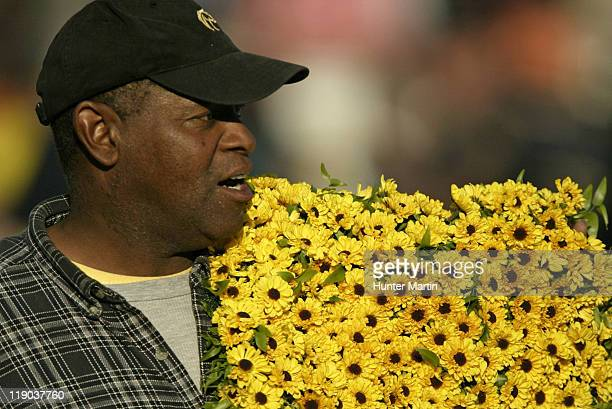 A trackman carries the blanket of Black Eyed Susans after the running of the 131st Preakness Stakes at Pimlico Race Track in Baltimore Maryland on...