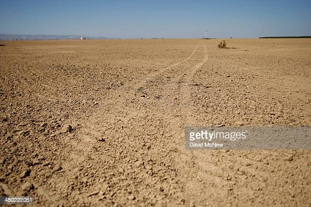 Tracks lead across a fallow field under which a crude oil pipeline passes near an oil field over the Monterey Shale formation where gas and oil...