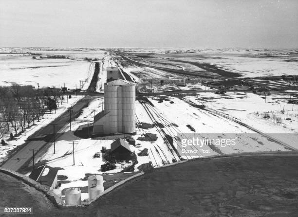 Tracks of Rock Island Railroad straddle Flagler's storage bins and head out eastward over rich wheat land which is overproducing farmers out of...