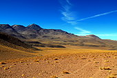 lonely track with many lanes over a lava field in the high mountains of the andes in chile with a panorama of volcano sairecabur