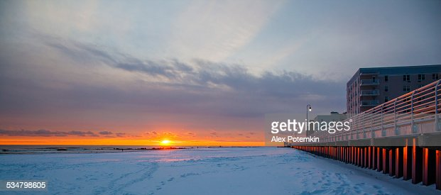Tracks on snowy ground at sunset on Long Beach next to wall.