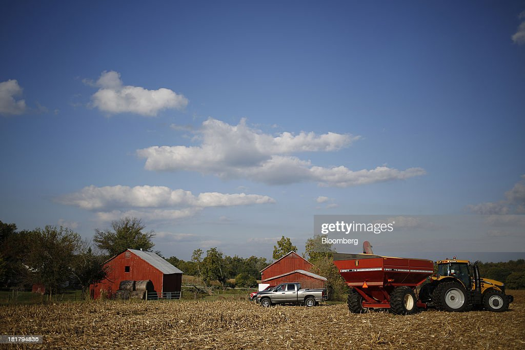 A tractor and a combine harvester trailer sit idle during a corn harvest on farm land leased to Tucker Farms in Shelbyville, Kentucky, U.S., on Tuesday, Sept. 24, 2013. Private exporters reported to the U.S. Department of Agriculture (USDA) export sales of 197,200 metric tons of corn for delivery to Mexico during the 2013 and 2014 marketing year. Photographer: Luke Sharrett/Bloomberg via Getty Images